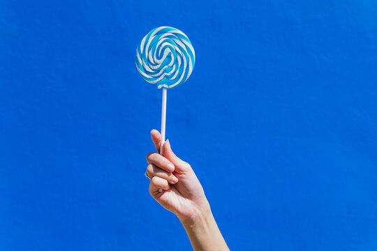 Crop woman with sweet lollipop on blue background