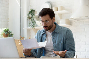 Obraz Man sit at table in domestic kitchen reading bad news in received correspondence paper letter feels stressed about bank debt, high taxes to pay, financial problems, changing terms of contract concept - fototapety do salonu