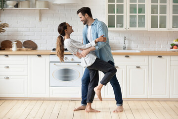Fototapeta Young beautiful mixed race couple home owners family celebrate relocation day housewarming dancing in modern cozy kitchen standing barefoot on warm floor feel happy. Romance, dating, bank loan concept obraz
