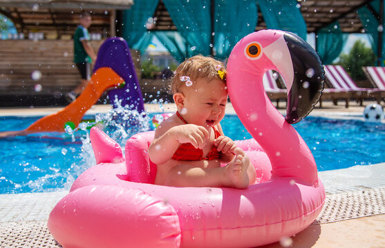 Baby swims in a circle in the pool. Selective focus.