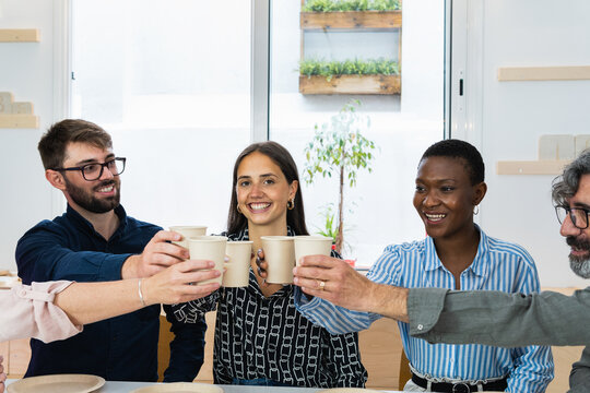 Diverse colleagues having lunch together in kitchen of office