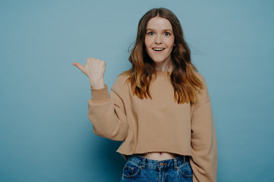 Excited young girl pointing finger somewhere posing over blue background