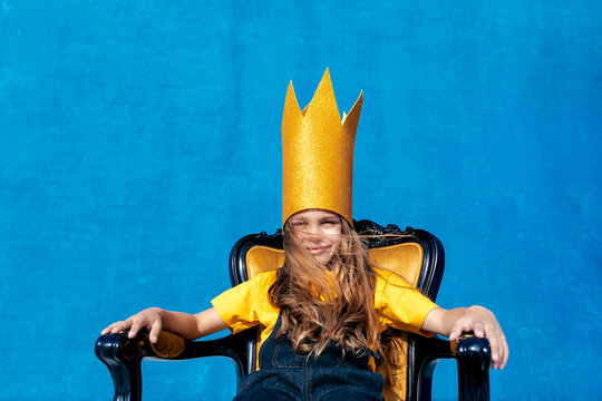 Cheerful teenager in paper crown sitting on throne