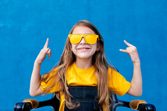 Cool teenager in sunglasses showing rock gesture