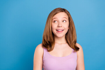Photo of optimistic brown hairdo teenager girl look empty space wear violet top isolated on blue color background Wall mural