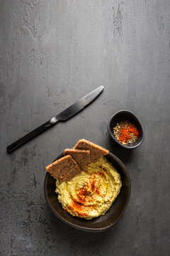 Chickpea hummus  decorated with sweet paprika on dark background with spice bowl and knife