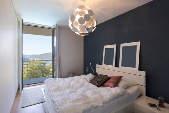 Elegant bedroom with large white bed and a balcony with a view of the valley with the lake