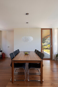 Front view dining room with wood table, leather chairs and dark hardwood floors. Stylish modern home