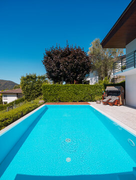 Front view pool with clear water and large green hedge, perfect for a vacation. Sunny day with blue skies.