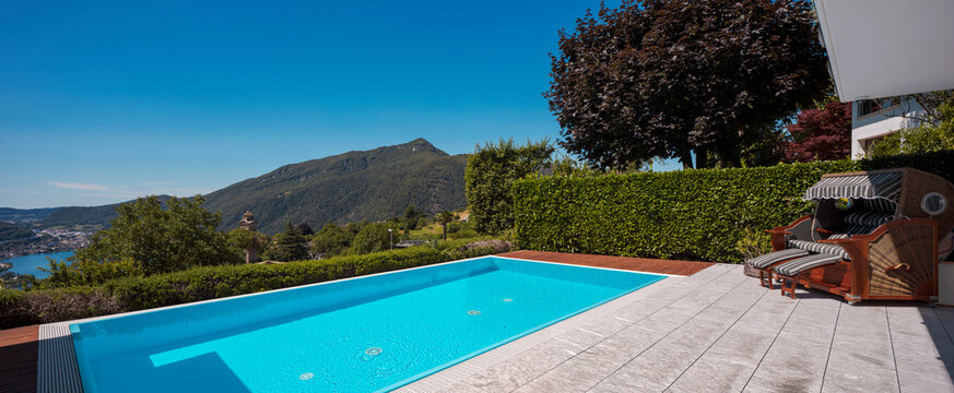 Large modern pool overlooking the lake and valley, nestled in the mountains of Switzerland. Sunny day