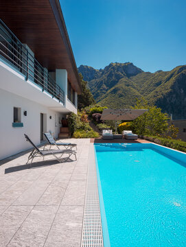 Modern two-story house with large pool overlooking the mountains.