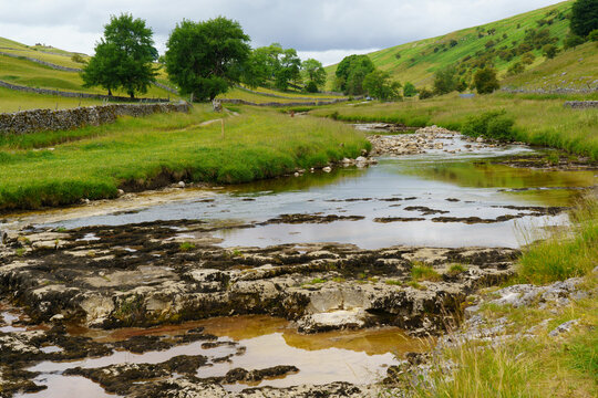 Low water level revealing jagged rocks on the River Wharfe, Kettlewell, Upper Wharfedale, North Yorkshire, England, UK.1