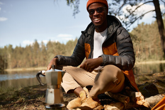 Excited afro american guy boiling water on fire for drink. Smiling man relaxing on nature in forest. Lead active lifestyle and leisure. Camping, hiking, travelling, explore new place concept