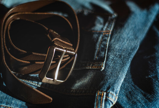 leather belt is a casual wardrobe accessory. Beautiful leather belt and jeans close-up. Men's brutal accessories, belt on a dark background with blurred depth of field, brown belt and denim