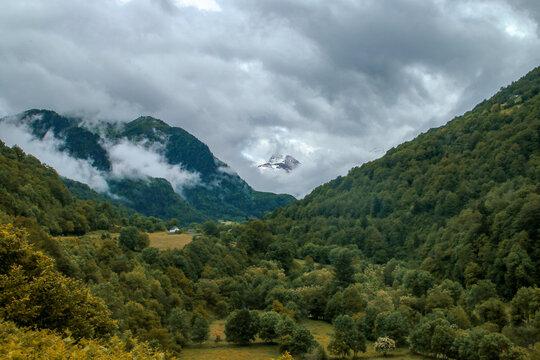 Vista de un paisaje natural en el lado norte de los Pirineos, Borce, Francia. Hermoso valle verde con nubes y montañas brumosas.