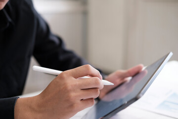 Fototapeta Business man with stylus pen writing on digital notepad obraz