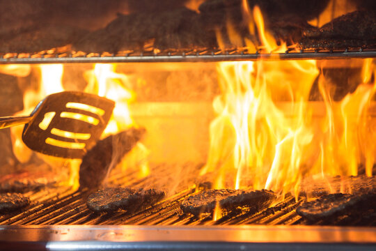 Flames Rise To Charbroil Sizzling Hamburgers On Grill At Event