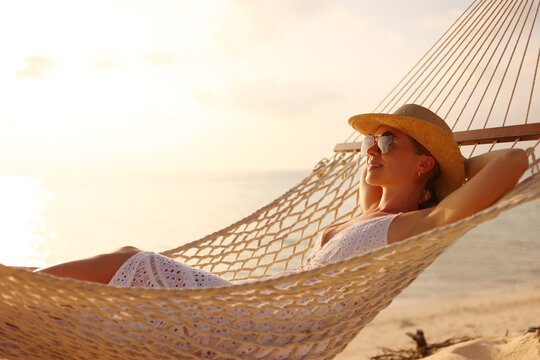 Young smiling female wearing straw hat and sunglasses keeping eyes closed lying in the hammock on the sandy beach and relaxing