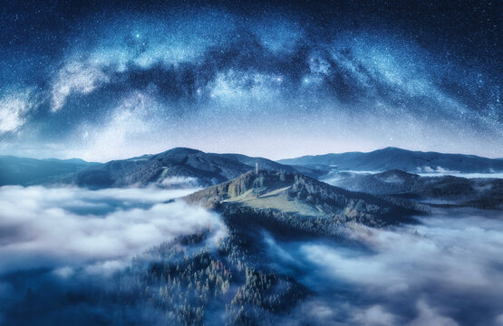 Milky Way arch and mountains in low clouds at starry night in summer. Landscape with sky with stars, arched Milky Way, trees on the hill in fog, mountain peaks. Space and galaxy. Aerial view. Nature