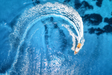 Obraz Aerial view of the speed boat in clear blue water at sunny day in summer. Top view from drone of fast floating yacht in mediterranean sea. Travel in Oludeniz, Turkey. Tropical landscape with motorboat - fototapety do salonu