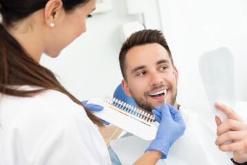 Obraz Man in stomatology clinic. Teeth whitening. - fototapety do salonu