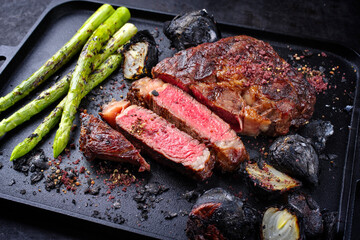 Fototapeta Modern style barbecue dry aged wagyu rib-eye beef steaks with green asparagus and charred onions served as close-up on a black cast iron design tray obraz