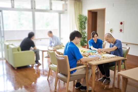 介護施設でレクリエーションをする高齢者と介護士