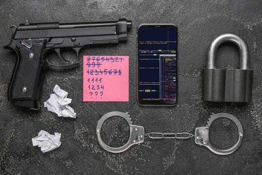 Mobile phone with gun, handcuffs, padlock and paper with passwords on dark background. Hacking concept