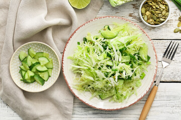 Plate with tasty cabbage salad and ingredients on light wooden table