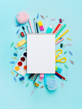 Notebook with stationary objects on blue background. Empty white paper sheet of notepad or sketchbook over shool supplies, isolated on blue. Vertical. Copy space for text or design. Top view, flat lay