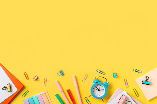 Education, back to school, freelancer work concept. School supplies, stationery accessories along bottom edge on yellow background. Flat lay, top view. Copy space