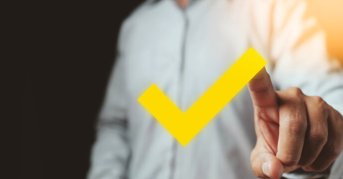 Businessman hand marking approved yellow check mark, Checklist concept