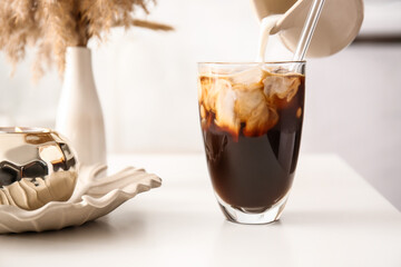 Fototapeta Pouring milk from jug into glass with tasty ice coffee on table, closeup obraz