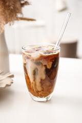 Fototapeta Glass of tasty ice coffee with milk on table obraz