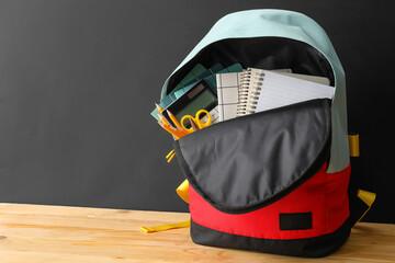 Fototapeta School backpack and stationery on table near blackboard obraz