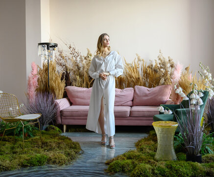 Pleasant young woman in a room with sofa in the middle of tall grass