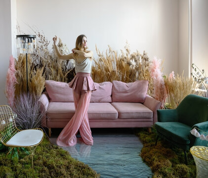 Pleasant young woman dancing in a room with sofa in the middle of tall grass