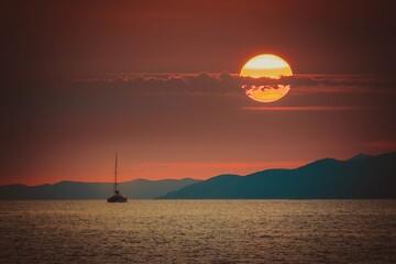 Obraz Pływający ludzie na morzu na tle ogromnego zachodzącego słońca - fototapety do salonu