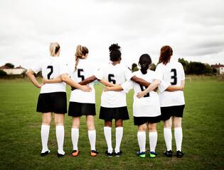 Fototapeta Female soccer players huddling and standing together obraz