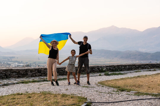 family with Ukrainian flag in the mountains