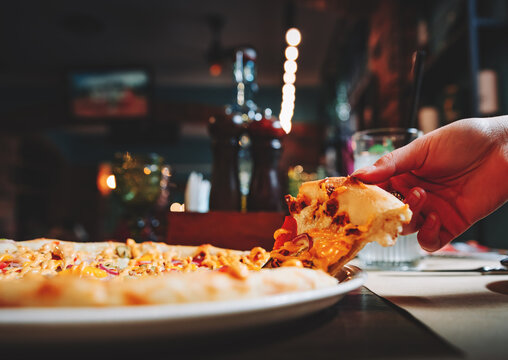 woman Hand takes a slice of meat Pizza with Mozzarella cheese, salami, Tomatoes, pepper, ham in cafe