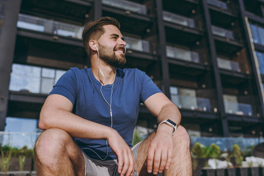 Bottom view young sporty strong fit sportsman man in headphones blue t-shirt listen music look aside warm up training outdoors sit on bench near black building in city centre in summer day morning