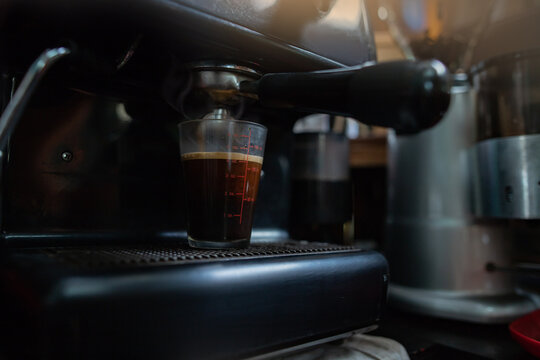 coffee machine brewing into a measuring cup with a meticulous process Surrounded by coffee-making facilities of a cafe.