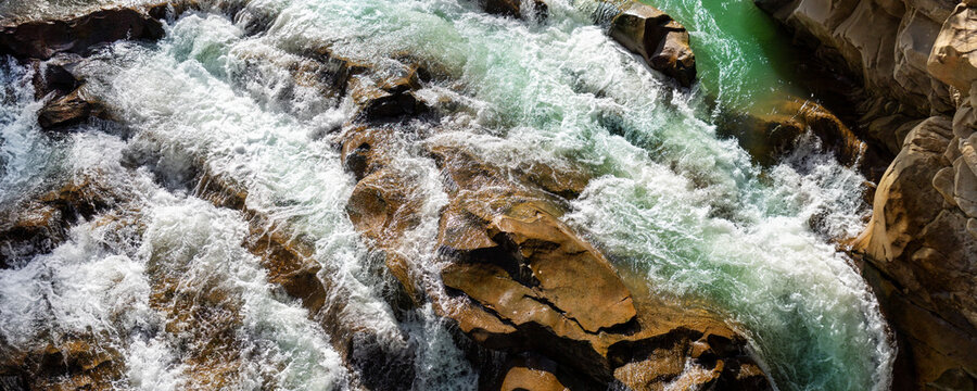 Close-up abstract texture above view of river torrent and clear fresh cold water flowing through mountain rocks in valley with foam bubbles on sunny day. Nature force power background. wide banner