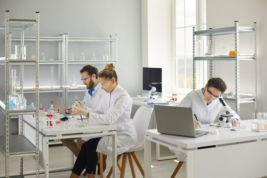 Group of medical scientists doing research in modern pharma or biotech science laboratory. Busy men and women in white lab coats and goggles sitting at tables and working with test samples
