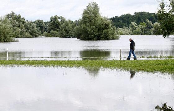 Man stands on a street in the flooded landscape near Maschwanden
