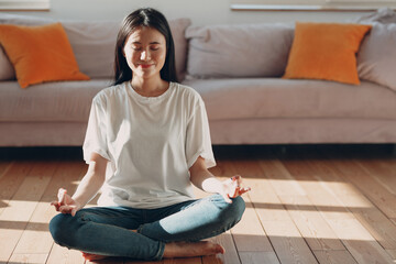 Asian woman doing yoga and zen like meditation lotus pose in casual wear at indoor living room...
