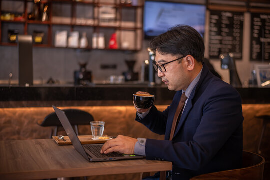 Asian businessman wearing suite and eyeglasses drink coffee , typing notebook for work at cafe restaurant.