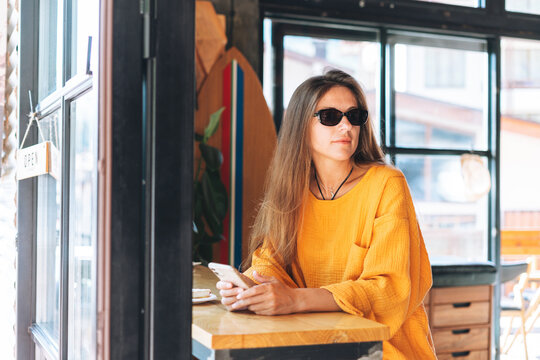 Young woman with long blonde hair wearing sunglasses and yellow longsleeve with mobile phone in her hands in cafe