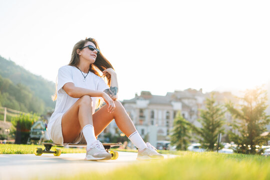 Slim young woman with long blonde hair in light sports clothes sitting with longboard in the outdoor skatepark at the sunset